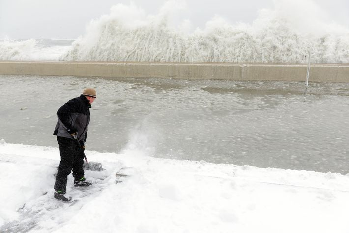 WINTHROP, MA - FEBRUARY 09: Mike Streeter shovels snow in his front yard as ocean water crashes over the sea wall just feet away on February 9, 2013 in Winthrop, Massachusetts. The powerful storm has knocked out power to 650,000 and dumped more than two feet of snow in parts of New England. (Photo by Darren McCollester/Getty Images)