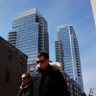 People walk by new apartment buildings near the waterfront in the rapidly developing neighborhood of Williamsburg on April 4, 2013 in the Brooklyn borough of New York City. Two Trees management, which owns the closed Domino Sugar factory, has unveiled new plans for the site that will include more than half a million square feet of office space, 228,000 square feet of open space and 2,284 apartments and retail space. The plan is a continuation of the rapid development of the Williamsburg waterfront which offers Manhattan views and water taxis to other parts of New York City.