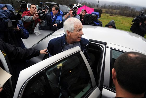 Former Penn State associate head football coach Jerry Sandusky is escorted to a police car, Wednesday, Dec. 7, 2011, in Bellefonte, Pa., after being arrested on new child sex abuse charges brought by two new accusers, including one who claims Sandusky molested him numerous times in a basement bedroom, according to authorities. The claims bring the number of Sandusky's alleged victims to 10, and he now faces more than 50 charges stemming from accusations he molested boys for years on Penn State property, in his home and elsewhere. (AP Photo/Centre Daily Times (Knight Ridder), Christopher Weddle)  ALTOONA MIRROR OUT; MAGS OUT