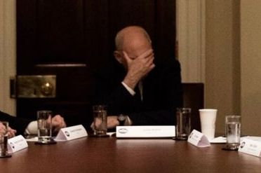 John Kelly with his hand over his face during a White House meeting.