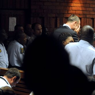 South Africa's Olympic sprinter Oscar Pistorius (2nd R) buries his face in his hands in the court room during his hearing on charge of murdering his model girlfriend Reeva Steenkamp on Valentine's Day on February 15, 2013 at the Magistrate Court in Pretoria. South African prosecutors will argue that Pistorius is guilty of premeditated murder in Steenkamp's death, a charge which could carry a life sentence.