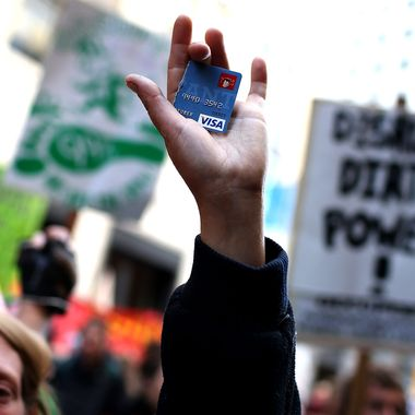 An Occupy Wall Street protestor holds up a cut up credit card during a demonstration on September 17, 2012 in San Francisco, California.  An estimated 100 Occupy Wall Street protestors staged a demonstration and march through downtown San Francisco to mark the one year anniversary of the birth of the Occupy movement.