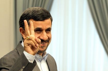 Iranian President Mahmoud Ahmadinejad flashes the V-sign for victory as he waits for the arrivak of Qatari Minister of State for International Cooperation Khaled bin Mohammed al-Attiyah in Tehran on October 13, 2011.