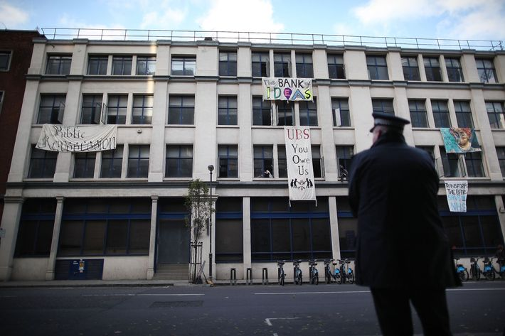 LONDON, ENGLAND - NOVEMBER 18: A policeman watches as Occupy London protestors hang banners from an unused building owned by UBS bank on November 18, 2011 in London, England. The Occupy London protest group are continuing to camp outside St Paul's Cathedral and nearby Finsbury Square in the heart of London's financial district. The deadline for those outside the cathedral to leave or face court action has passed. (Photo by Peter Macdiarmid/Getty Images)