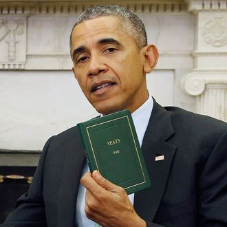 U.S. President Obama holds a book of poetry given to him by Ireland's PM Kenny during their meeting in the Oval Office as part of a St. Patricks Day visit at the White House in Washington