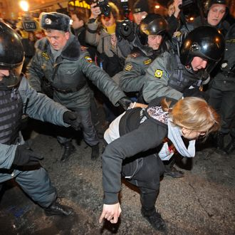 Riot police detain a Russian opposition activist taking part in an unauthorized rally, on Triumfalnaya Square in central Moscow, late on December 6, 2011. Opposition leaders defied the Russian authorities today by organizing a second mass protest in two days against Vladimir Putin's 12-year rule, despite warnings of a police crackdown and the jailing of one of the organizers.