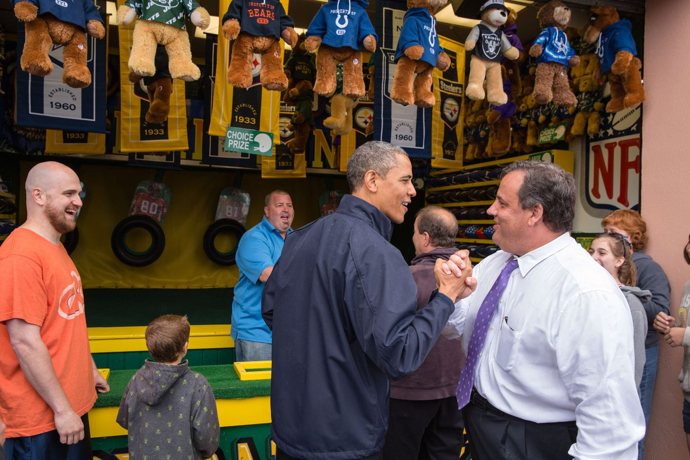 "In this handout provided by the White House, U.S. President Barack Obama (C) congratulates New Jersey Governor Chris Christie (R) while playing the ""TouchDown Fever"" arcade game along the Point Pleasant boardwalk May 28, 2013 in Point Pleasant Beach, New Jersey.  Seven months after Superstorm Sandy devastated the region, President Obama declared that the Jersey Shore is back in an appearance with the governor."