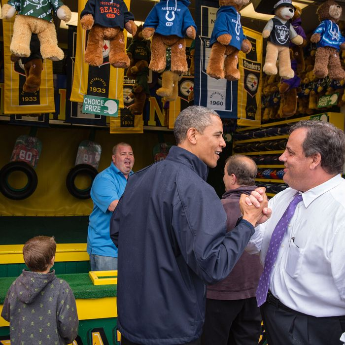 In this handout provided by the White House, U.S. President Barack Obama (C) congratulates New Jersey Governor Chris Christie (R) while playing the