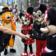 A tourist (L) tips a Minnie Mouse character after he posed for a photograph with the cartoon figures July 28, 2014 in New York's Times Square. The panhandler characters pose for tourists and work for tips, which can sometimes lead to disputes, like the Spider-Man character arrested on July 26, for assaulting a police officer after an argument with a tourist over the amount of the tip.   AFP PHOTO/Stan HONDA        (Photo credit should read STAN HONDA/AFP/Getty Images)