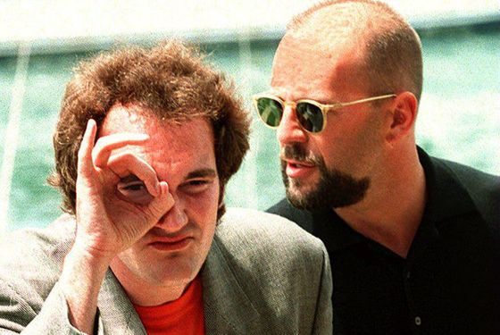 "CANNES, FRANCE:  US film director Quentin Tarantino (L) and compatriot actor Bruce Willis pose for photographers 21 May 1995 prior to the screening of their movie ""Pulp Fiction"" at the 47th Cannes Film Festival in France. (Photo credit should read PATRICK HERTZOG/AFP/Getty Images)"