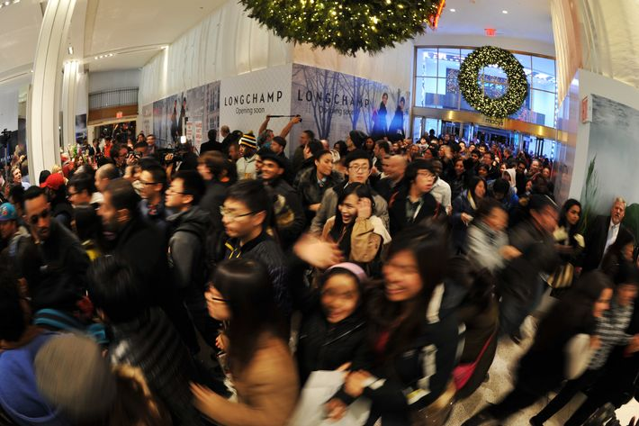 People rush into Macy's department store as they open at midnight (0500 GMT) on November 23, 2012 in New York to start the stores'