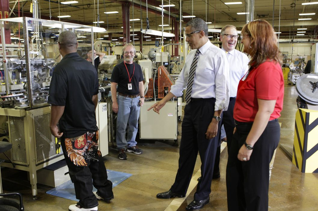 US President Barack Obama (R) points to a worker's jeans as tours the Honeywell Golden Valley facility in Minneapolis, Minnesota on June 1, 2012.