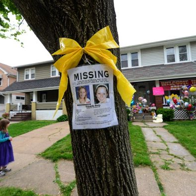 A missing person sign displaying portraits of Amanda Berry , one of the three women held captive for a decade, stands in front of her sister's house May 7, 2013 in Cleveland, ohio. (Emmanuel Dunande/AFP/Getty Images)