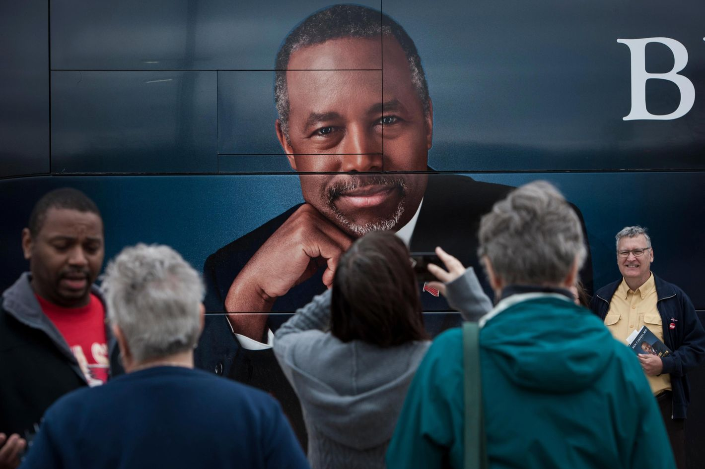Supporters of Dr. Ben Carson stand near his book tour bus in Ames, Iowa