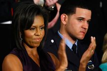 U.S. First Lady Michelle Obama applauds her husband, U.S. President Barack Obama, while he addresses a joint meeting of Congress as Philadelphia Police Officer Richard DeCoatsworth (R) stands by her February 24, 2009 at the U.S. Capitol in Washington, DC. In his remarks Obama was expected to address the topics of the struggling U.S. economy, the budget deficit, and health care.