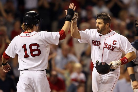 Json Varitek of the Boston Red Sox celebrates his two run homer with teammate Josh Reddick in the eighth inning against the New York Yankees on August 31, 2011 at Fenway Park in Boston.