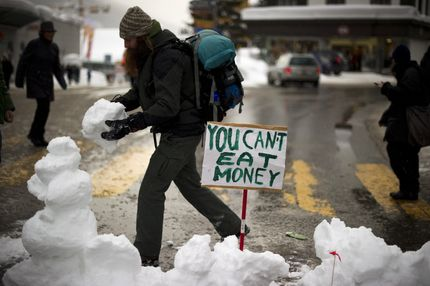 """An """"Occupy WEF"""" protester builds a snowman across the street during a protest on January 28, 2012, against the World Economic Forum (WEF) annual meeting on January 28, 2012 in the Swiss resort of Davos.   AFP PHOTO / FABRICE COFFRINI (Photo credit should read FABRICE COFFRINI/AFP/Getty Images)"""