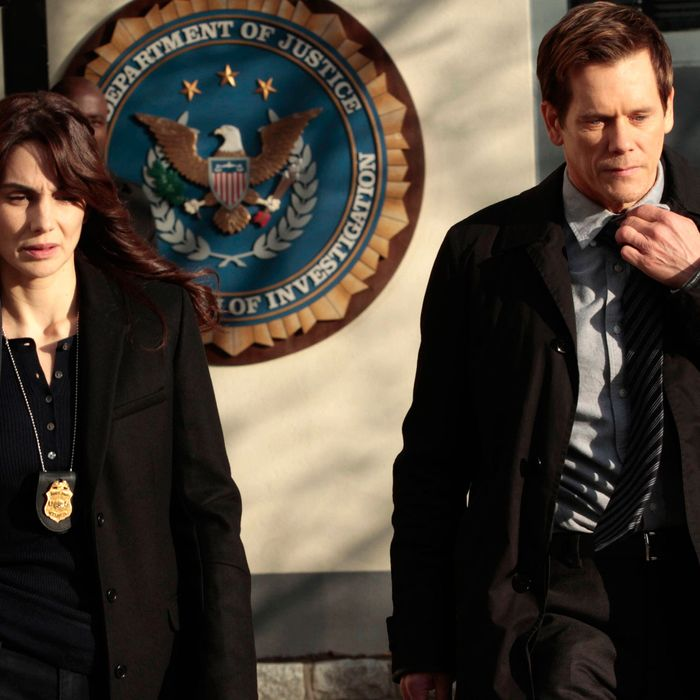 THE FOLLOWING: Special Agent Parker (Annie Parisse, L) and Ryan (Kevin Bacon, R) leave the FBI bureau in the