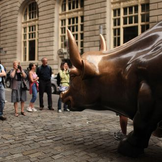People pose for pictures beside the Wall Street bull, a bronze bull statue that symbolizes a