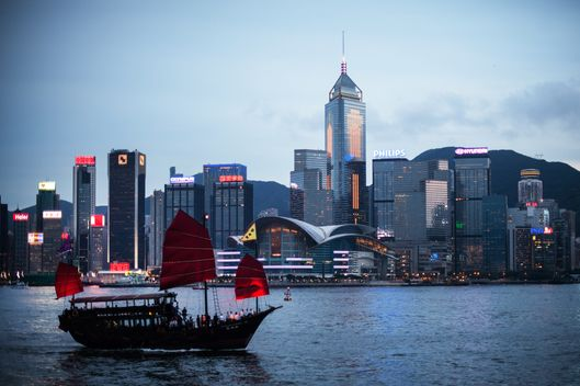 A junk sails on Victoria Harbour in front of the city's skyline in Hong Kong on June 3, 2013. The harbour waters is mostly crowded and often see high-speed hydrofoils vying for space with tourist junks, luxury yachts and a century-old public ferry system that connect Hong Kong island to the Kowloon peninsula.
