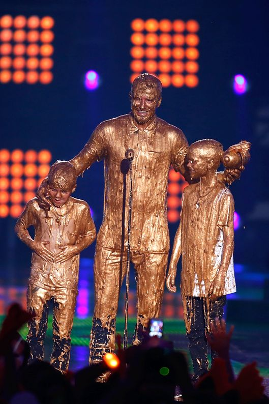 LOS ANGELES, CA - JULY 17:  (L-R) Cruz Beckham, David Beckham and Romeo Beckham get slimed onstage  at Nickelodeon Kids' Choice Sports Awards 2014 at Pauley Pavilion on July 17, 2014 in Los Angeles, California.  (Photo by Joe Scarnici/WireImage)
