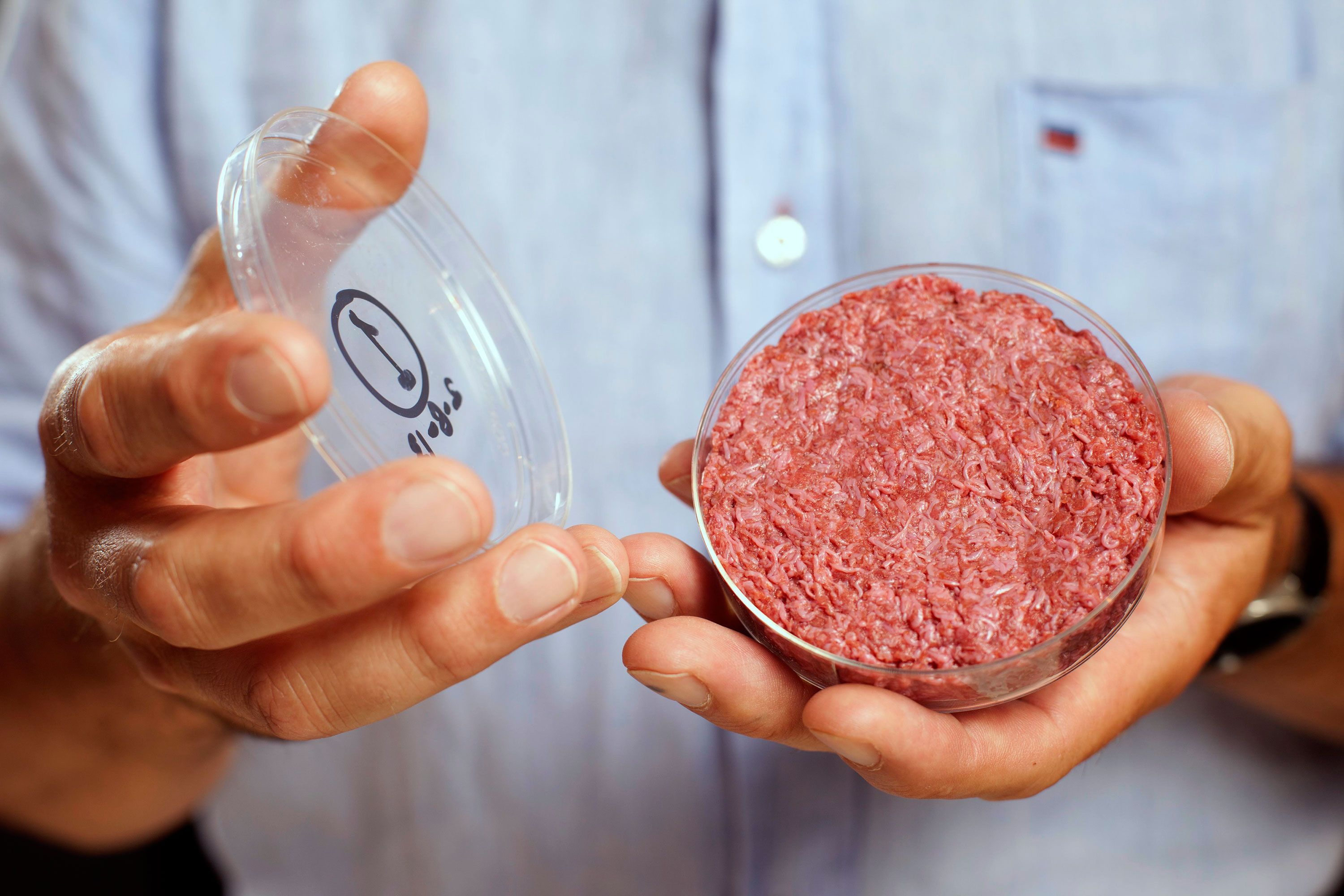 Professor Mark Post holds the world's first lab-grown beef burger during a launch event in west London