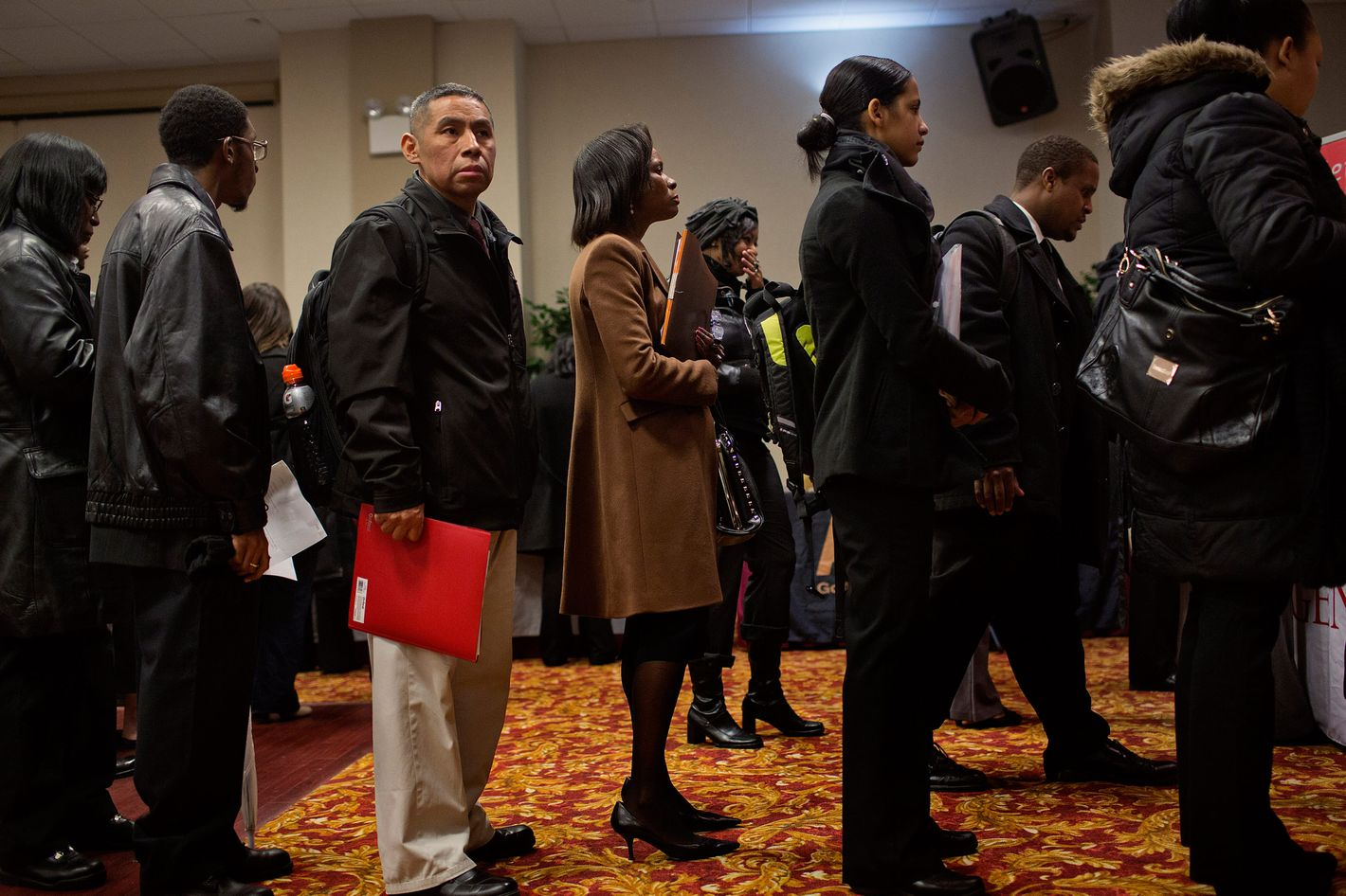Job seekers wait to talk to recruiters and fill out applications at a job fair in New York, U.S., on Thursday, Jan. 16, 2014.
