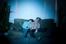 Young couple fallen asleep in front of tv