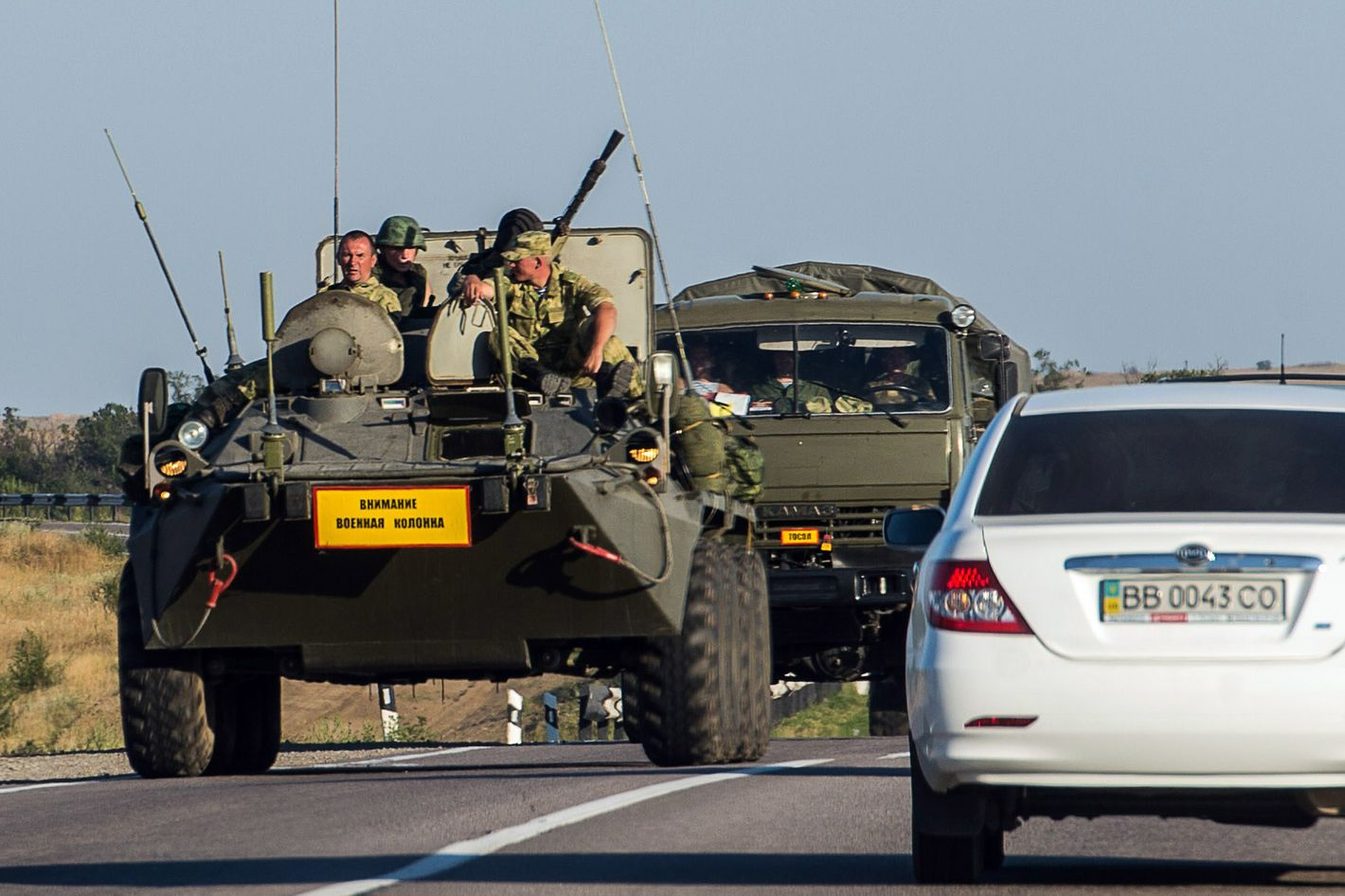 """A Ruissian armoured personnel carrier (APC) leads a column of military vehicles on a road near the town of Kamensk-Shakhtinsky in the Rostov region, some 30 km from the Russian-Ukrainian border, on August 15, 2014. Ukrainian officials were preparing to inspect a massive Russian """"aid"""" convoy bound for the conflict-torn east on August 15 after Russian armoured vehicles crossed the border, fuelling fears Moscow is trying to bolster the unravelling insurgency. The Ukrainian military had announced that checks had begun on the near 300-truck convoy but later said only that 59 border and customs officials had arrived at a Russian border post to prepare to carry out the inspections. AFP PHOTO / DMITRY SEREBRYAKOV        (Photo credit should read DMITRY SEREBRYAKOV/AFP/Getty Images)"""