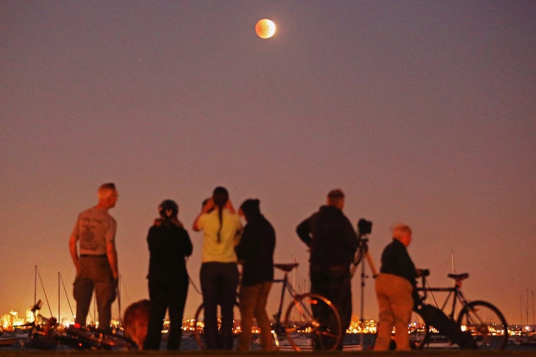 "MELBOURNE, AUSTRALIA - APRIL 15:  People watch as the 'Blood Moon' rises over the water in Wlliamstown on April 15, 2014 in Melbourne, Australia. The Lunar Eclipse, resulting in the Moon appearing to be an orange-red colour is due to a perfect alignment of the Sun, Earth and Moon, otherwise known as ""syzygy"".  (Photo by Scott Barbour/Getty Images)"