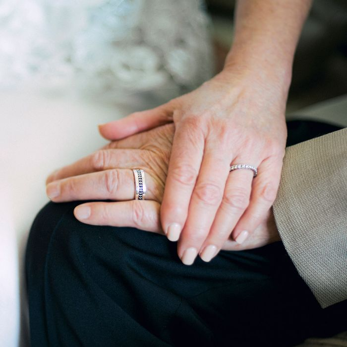 An elderly couple with wedding bands.