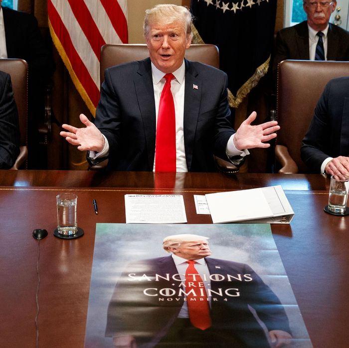 President Donald Trump in front of the meme poster.