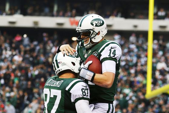 Greg McElroy #14 of the New York Jets celebrates with  Konrad Reuland #87 after throwing his first touchdown in the NFL to  Jeff Cumberland #86 against the Arizona Cardinals during their game at at MetLife Stadium on December 2, 2012 in East Rutherford, New Jersey. The Jets won 7-6.