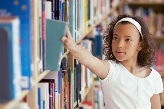 Girl selecting book from library shelves