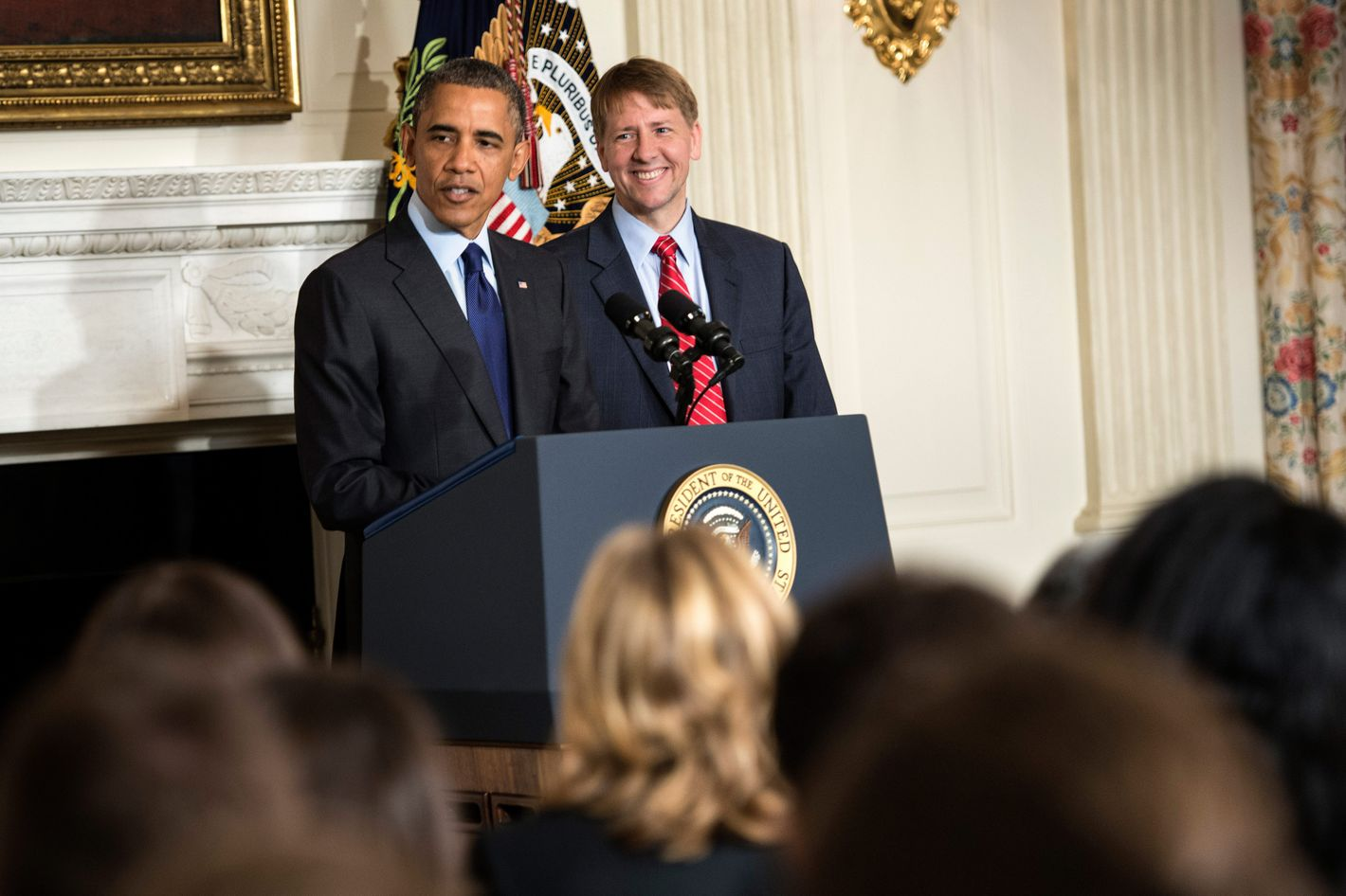 Consumer Financial Protection Bureau Director Richard Cordray listens to US President Barack Obama make a statement in the State Dining Room of the White House July 17, 2013 in Washington, DC. Obama spoke about the recent confirmation of Cordray as the Director of the Consumer Financial Protection Bureau, who was sworn in earlier today.