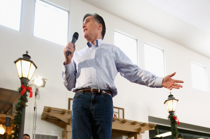 MASON CITY, IA - DECEMBER 29:  Former Massachusetts Governor and Republican presidential candidate Mitt Romney stands in a chair as campaign staff member Garrett Jackson holds it steady during a campaign event at Music Man Square December 29, 2011 in Mason City, Iowa. Recent state-wide polls put Romney and fellow candidate Rep. Ron Paul (R-TX) close going into next week's first-in-the-country Iowa Caucuses, a litmus test for the GOP hopefuls.  (Photo by Chip Somodevilla/Getty Images)