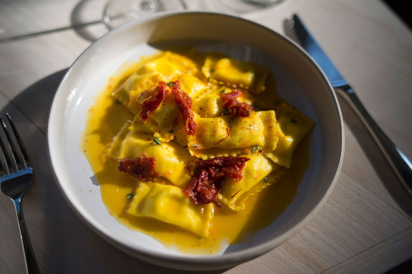 Sheep's-milk-cheese-filled pasta with saffron, tomato sugo, and honey.