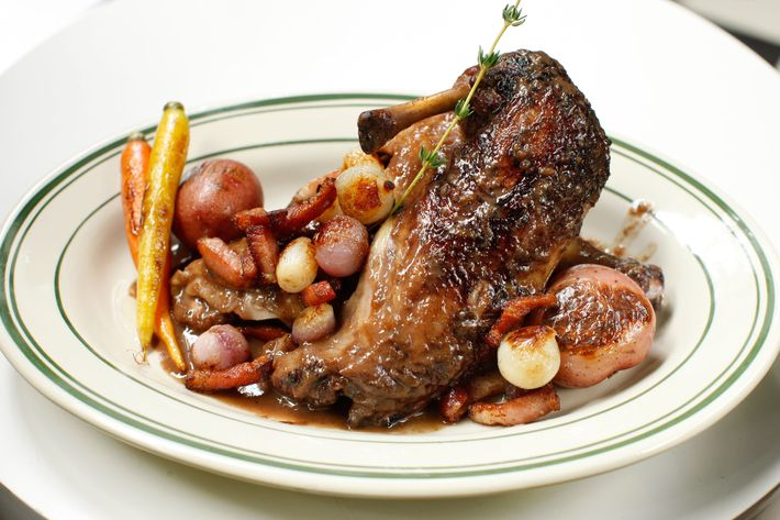 Coq au vin with pearl onions and bacon lardons.