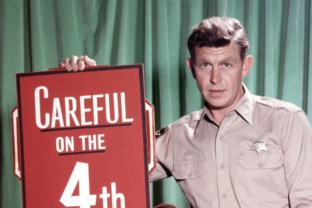 Andy Griffith, US actor, and Ron Howard, US actor, pose beside a large firework, with a sign reading 'Careful on the 4th' in a publicity portrait issued for the US television series, 'The Andy Griffith Show', USA, circa 1963. The sitcom starred