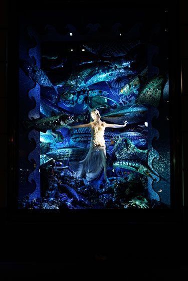 "This window, called ""Testing the Waters,"" is covered in hand-cut Italian mosaic tile and is the most labor-intensive single window display in Bergdorf Goodman history. The mannequin wears a seashell dress from Alexander McQueen's spring 2012 collection."