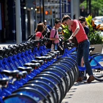 A couple get their Citi Bike bicycles from a station near Union Square as the bike sharing system is launched May 27, 2013 in New York. About 330 stations in Manhattan and Brooklyn will have thousands of bicycles for rent.