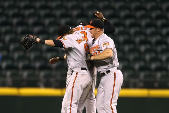 Outfielders Nate McLouth #9, Adam Jones #10, and Lew Ford #51 of the Baltimore Orioles celebrate after defeating the Seattle Mariners 4-2 in eighteen innings at Safeco Field on September 18, 2012 in Seattle, Washington.