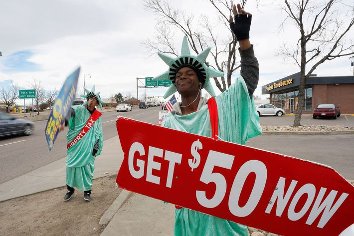 Manuel Martinez (R) and Jose, both dressed like the Statue of Liberty, wave signs advertising the Liberty Tax preparation business in Denver February 14, 2015. Tax season is in full swing in the U.S. with federal tax returns due to be filed April 15th. REUTERS/Rick Wilking (UNITED STATES - Tags: SOCIETY BUSINESS) --- Image by ? RICK WILKING/Reuters/Corbis