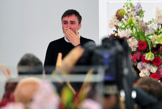 Belgian designer Raf Simons blows a kiss to the audience as he cries at the end of the Jil Sander Fall-winter 2012-2013 collection on February 25, 2012 during the Women's fashion week in Milan. The company announced the day before German fashion designer Jil Sander is set to make a return to the company that bears her name nearly eight years after resigning, with Simons leaving his position of creative director on February 27.  AFP PHOTO / GIUSEPPE CACACE (Photo credit should read GIUSEPPE CACACE/AFP/Getty Images)