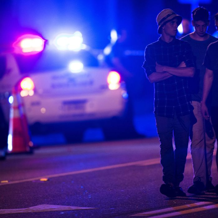 People walk by a police roadblock near the Pulse nightclub on June 12, 2016 in Orlando, Florida. People close to the gunman behind the attack on a gay nightclub in Florida that left 50 dead, paint a picture of a violent and prejudiced young man.