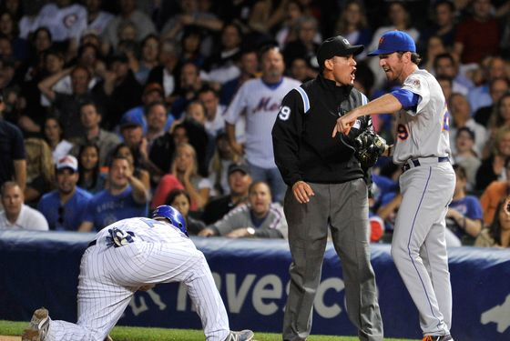 CHICAGO, IL - JUNE 26:  First baseman Ike Davis #29 of the New York Mets (R) argues with first base umpire Manny Gonzalez (C) after Gonzalez called Steve Clevenger #51 of the Chicago Cubs safe at first on a pickoff play during the eighth inning at Wrigley Field on June 26, 2012 in Chicago, Illinois. Gonzalez ejected Davis for arguing.  (Photo by Brian Kersey/Getty Images)