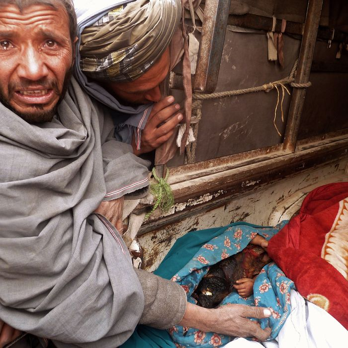 A mourner cries over the bodies of Afghan civilians, allegedly shot by a rogue US soldier, seen loaded into the back of a truck in Alkozai village of Panjwayi district, Kandahar province on March 11, 2012. An AFP reporter counted 16 bodies -- including women and children -- in three Afghan houses after a rogue US soldier walked out of his base and began shooting civilians early Sunday. NATO's International Security Assistance Force said it had arrested a soldier