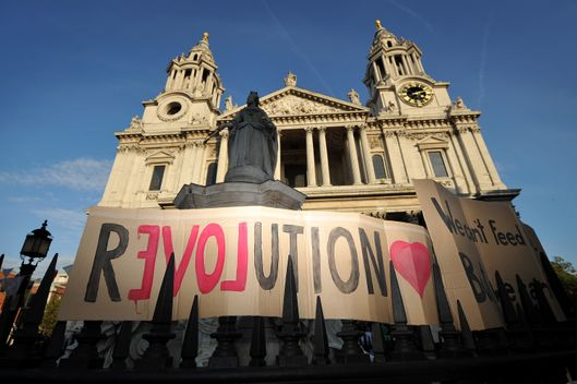"A banner reading 'Revolution' is displayed  in front of St Paul's Cathedral in the city of London on October 16, 2011 as part of a global day of protests inspired by the ""Occupy Wall Street"" and ""Indignant"" movements. Several hundred anti-capitalist protesters set up camp before St Paul's Cathedral, pitching tents, politely waving placards, and even setting up a makeshift kitchen.  AFP PHOTO/Ben Stansall (Photo credit should read BEN STANSALL/AFP/Getty Images)"