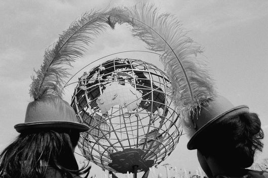 Souvenir hats on the heads of two young visitors to the New York World's Fair frame the fair's symbol, the Unisphere in New York, May 11, 1965. Fair officials are hoping for a record turnout during this second and last year of the fair. (AP Photo/Dave Pickoff)