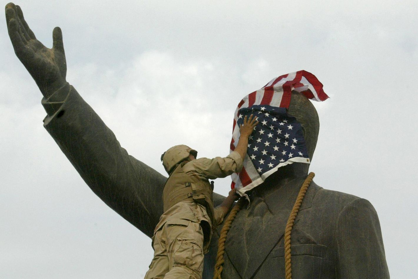 Baghdad, IRAQ: TO GO WITH AFP STORIES ON ANNIVERSARY OF THE FALL OF BAGHDAD: (FILES) A US Marine covers the face of Iraqi President Saddam Hussein's statue with the US flag in Baghdad's al-Fardous square 09 April 2003. The world was stunned when iconic images of US marines and Iraqis pulling down a statue of Saddam Hussein flashed across television screens. The toppling of the statue was immediately seized on as symbolising the overthrow of one of the world's most notorious despots. But four years later, some Iraqis say the symbol has turned into a sign of the brutal violence that has devastated their country. The square and its surroundings have changed dramatically since the launch of the invasion in March 2003.  AFP PHOTO/Ramzi HAIDAR (Photo credit should read RAMZI HAIDAR/AFP/Getty Images)